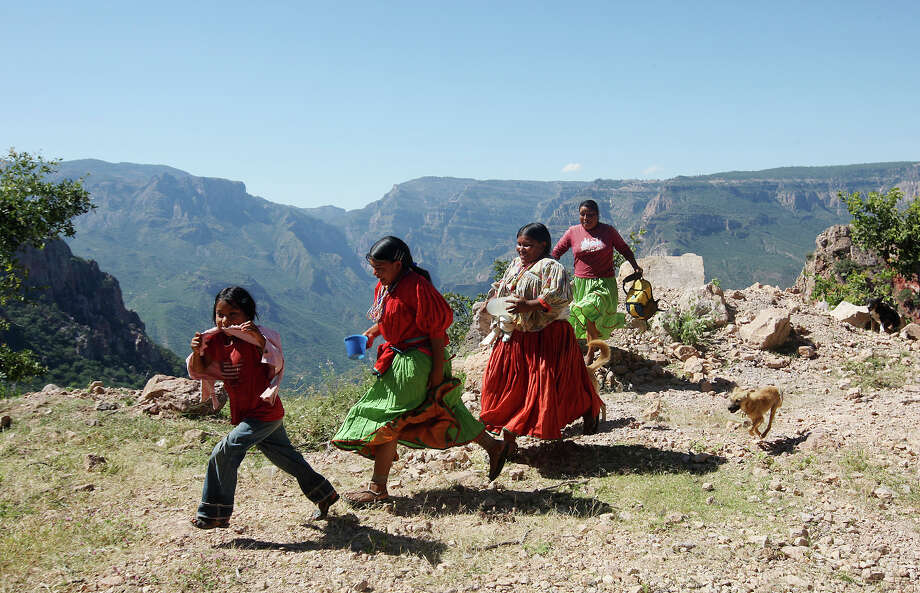Tarahumara women and children run to catch a ride on their way to the isolated settlement of Santa Rita, Mexico in the Sierra Madre Occidental mountains of Chihuahua, Monday, Oct. 8, 2012. An estimated 70,000 Tarahumara, who refer themselves as the Raramuri, occupy the Sierra Tarahumara. They exist in small community groups and rely on harvest of corn, beans and squash supplemented with livestock and chickens. Photo: Jerry Lara, San Antonio Express-News / © 2012 San Antonio Express-News