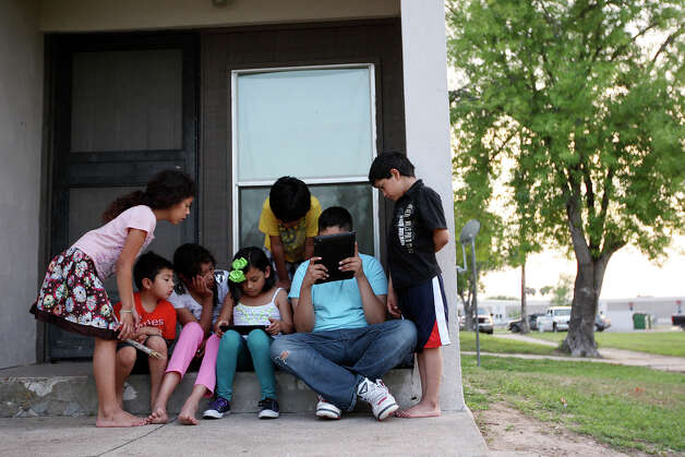 Friends and family surround Crystal Zivec, 8, center left, and Eric Garcia, 12, as they play games on iPads at the Memorial Apartments in McAllen, Tuesday, April 3, 2012. The McAllen Independent School District began handing out iPads and iPod Touch to over six thousand of the students in February. They plan on handing out the devices to the entire student population of 27,000 over the next 12 months. The Memorial Apartments consists of low-income housing where internet access is sparse. Students who live in the apartments rely on the few who do have access in their units. Photo: Jerry Lara, San Antonio Express-News / © San Antonio Express-News