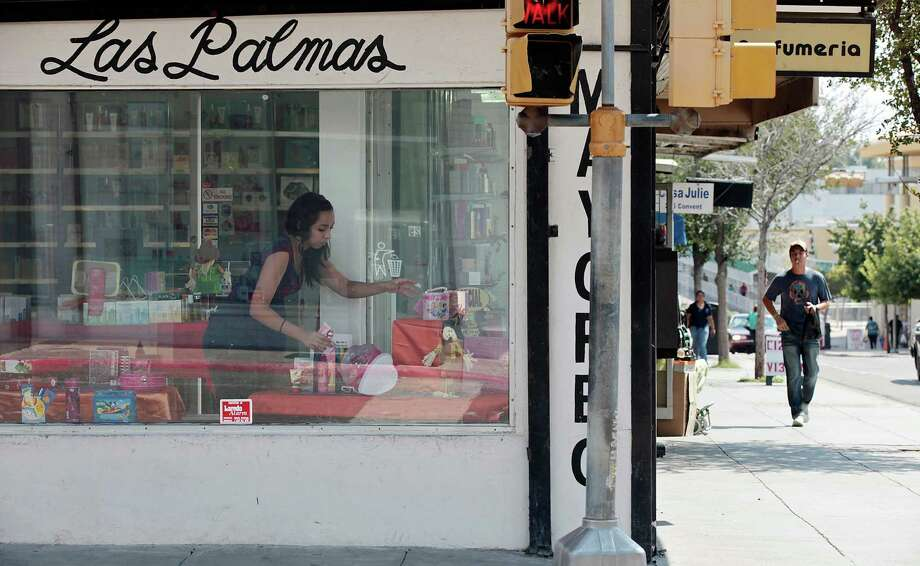 An employee works on a storefront display at a perfume store one block away from International Bridge One in downtown Laredo, Wednesday, Sept. 19, 2012. Downtown businesses have suffered with low sales due to various factors including the drug war across the Rio Grande in Nuevo Laredo. Photo: Jerry Lara, San Antonio Express-News / © 2012 San Antonio Express-News