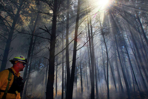 Hillsboro, Texas firefighter David Pruitt (left) monitors a controlled burn near Bastrop, Texas Friday October 19, 2012 during the 15th annual Capital Area Interagency Wildfire Academy at Camp Swift. More than 475 firefighters, including some from the San Antonio and Bexar County areas, are attending the academy which runs from October 12 to October 25. The academy is coordinated by Texas A&M Forest Service in partnership with local, state and federal agencies. Photo: John Davenport, San Antonio Express-News / ©San Antonio Express-News/Photo Can Be Sold to the Public