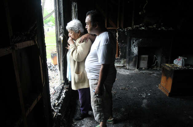 "Rachel C. Martinez (left) and her son Frank T. Martinez look out the window of Rachel Martinez's home after it burned up at about 1:30 a.m. last night while Frank Martinez was sleeping in the home. Rachel Martinez is Frank Martinez's mother and she owns the home, located at 2313 Texas Avenue. Frank Martinez,43, who has diabetes and is epileptic, said he woke up to see flames and smoke in the house after his next door neighbor Raymond Henerie began pounding on his front door. The Martinez family lost four cats and one dog in the fire. ""I never want to go through this again,"" Frank Martinez, said. The fire started because of an electrical problem, Frank Martinez said. Photo: John Davenport, San Antonio Express-News"