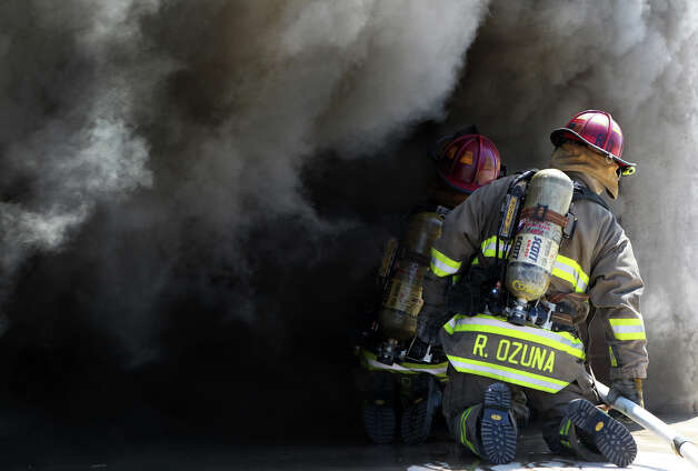 San Antonio firefighters put out a simulated dormitory fire Tuesday August 14, 2012 during a demonstration at the San Antonio Fire Department Training Academy for college students from Trinity and St. Mary's Universities. Resident assistants (RAs) from the schools attended a fire safety workshop at the academy to help them learn and prepare in case of a campus fire. This simulated dorm fire became fully engulfed in seven minutes. Photo: John Davenport, San Antonio Express-News