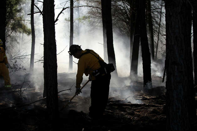 A firefighter works a controlled burn near Bastrop, Texas Friday October 19, 2012 during the 15th annual Capital Area Interagency Wildfire Academy at Camp Swift. More than 475 firefighters, including some from the San Antonio and Bexar County areas, are attending the academy which runs from October 12 to October 25. The academy is coordinated by Texas A&M Forest Service in partnership with local, state and federal agencies. Photo: John Davenport, San Antonio Express-News