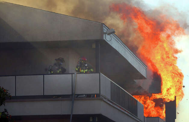 San Antonio firefighters work on the upper floor of the Studio 6 Extended Stay motel on U.S. 281 north near Rhapsody street during a multiple alarm fire that took place there Friday April 20, 2012. Firefighters experienced low water pressure there according to fire deparment scanner traffic. Photo: John Davenport, San Antonio Express-News