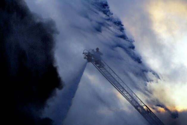 San Antonio Firefighters battle a three-alarm warehouse blaze Friday August 17, 2012 on the 9500 block of Ball. The fire broke out about 4:30 a.m. and a nearby motel on IH-35 was evacuated. Photo: John Davenport, San Antonio Express-News