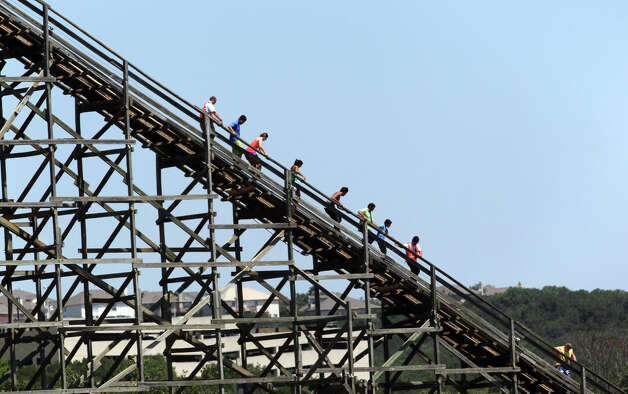 People at Six Flags Fiesta Texas climb down the Rattler roller coaster Friday August 3, 2012 after technical problems kept the coaster from finishing this ride. Once billed as the fastest and tallest wooden roller coaster in the world, the ride is currently scheduled to carry its last rider on August 5, 2012. These roller coaster riders were stuck for about 40 minutes before workers at the park helped them climb down off the ride. Park spokesperson Sydne Purvis said the cause of the incident was a computer problem. Photo: John Davenport, San Antonio Express-News / John Davenport/©San Antonio Exp