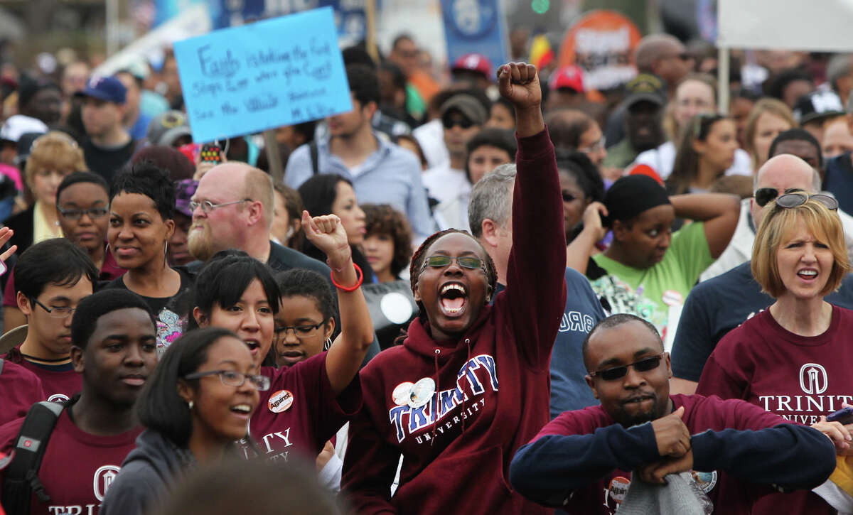Trinity University students (bottom, foreground) take part in the Martin Luther King, Jr. March as marchers come close to Pittman Sullivan Park on Monday January 16, 2012.