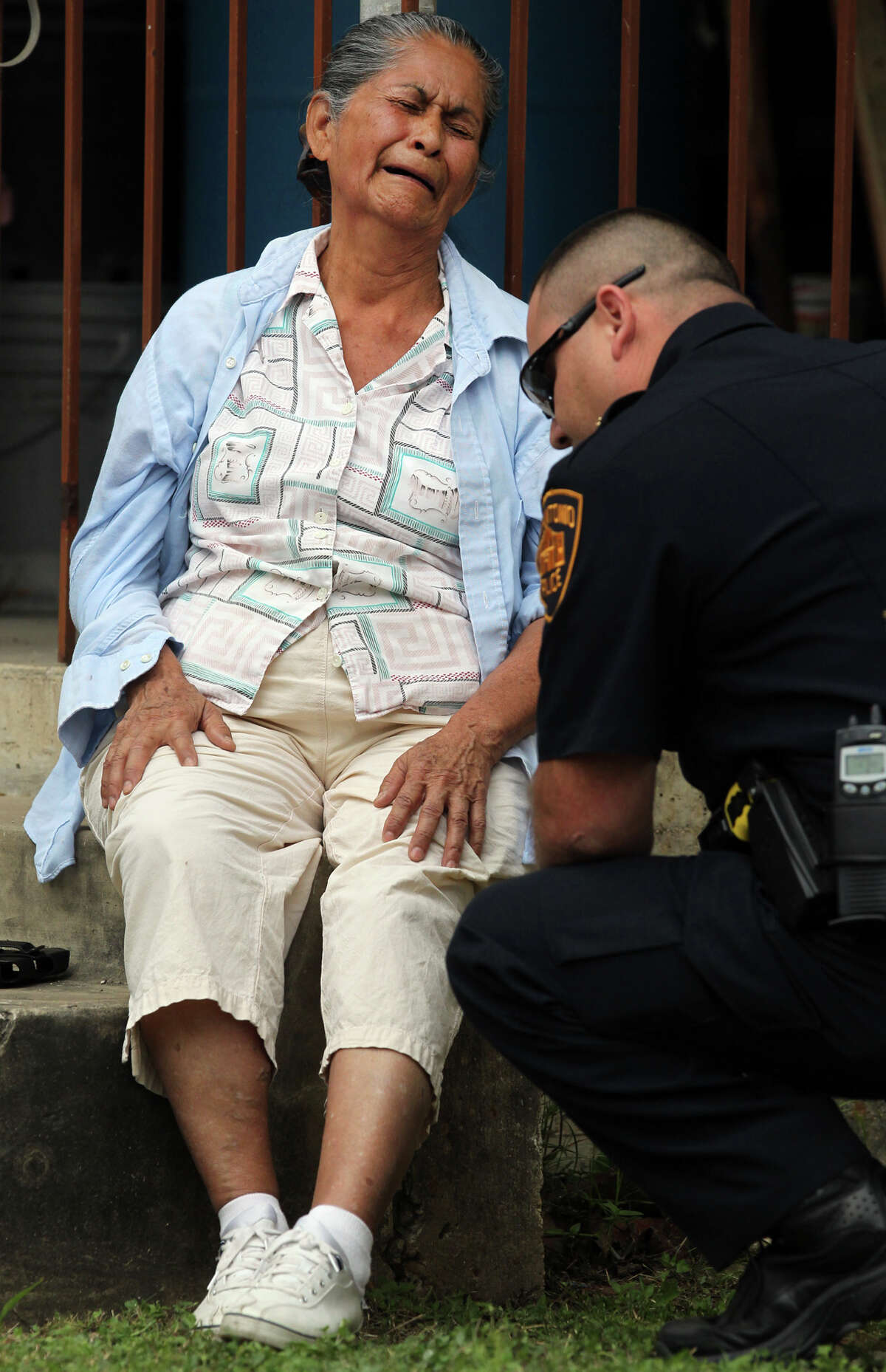 A San Antonio police officer consoles a woman described by police as the common law wife of a man who was fatally wounded Monday April 16, 2012 at 5600 block of South Flores while he cutting down foliage with a power tool that cuts with a circular steel blade. The 83-year-old man died at the scene after San Antonio firefighters tried to save him.