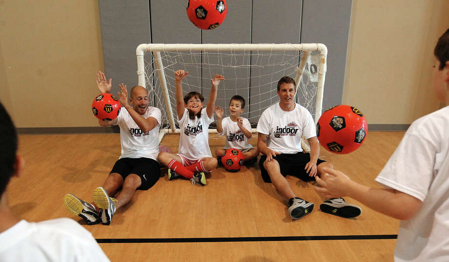 San Antonio Scorpions' Hans Denissen (left) and Daryl Sattler (right) join 11-year-old Emily Carter (second from left) and seven-year-old Aiden Strack (second from right) in blocking shots at the goal as Morgan's Wonderland hosts a soccer clinic for special needs children with appearances and coaching by San Antonio Scorpions soccer players on Thursday, July 26, 2012. Several players were on hand to boost the spirits of the young participants with coaching and encouragement. Representatives from Morgan's Wonderland said they intend on offering more of the soccer clinics in the near future. Photo: Kin Man Hui, San Antonio Express-News / ©2012 San Antonio Express-News