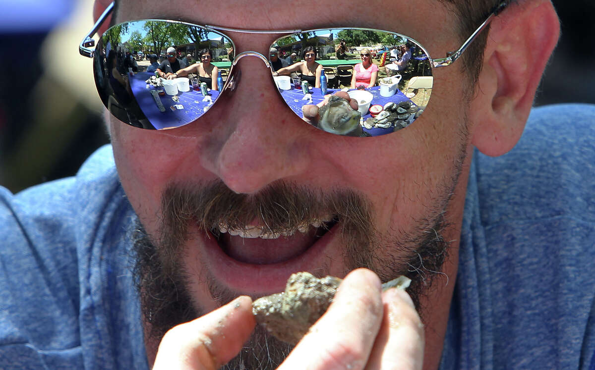Ryan Wannemacher gets ready to devour a baked oyster as the scene of friends and shucked oysters reflect off his sunglasses at the 2012 Fiesta Oyster Bake at St. Mary's University on Saturday, Apr. 21, 2012. Proceeds from the event go toward scholarships and university programs.
