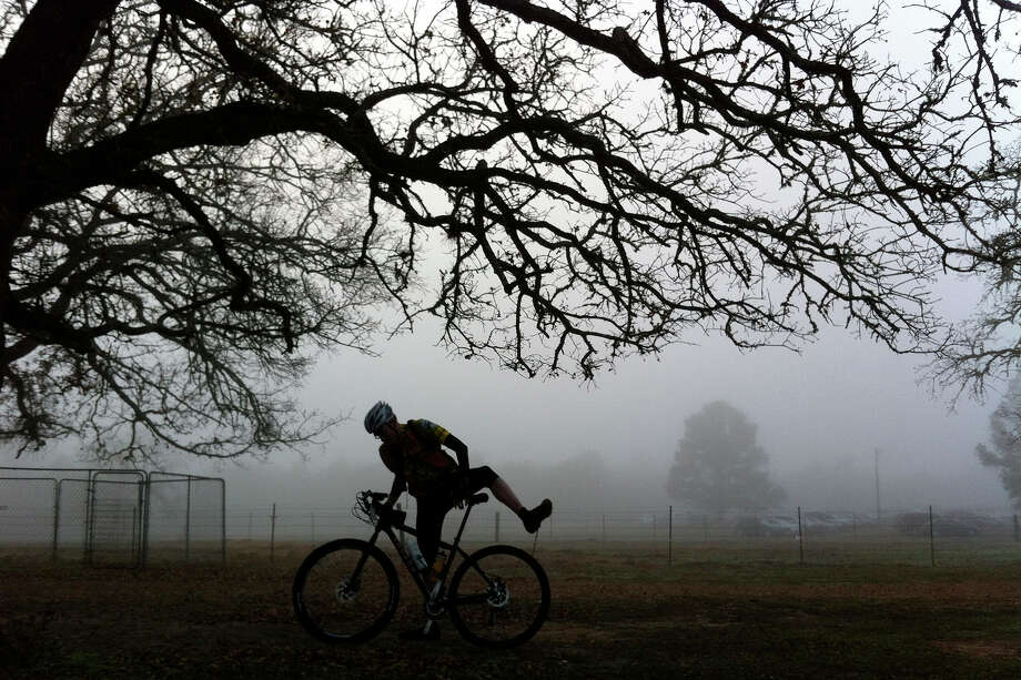 In the early morning fog, a rider mounts his bicycle at the start of the Excruciation Exam mountain bike race at Bluff Creek Ranch in Warda. Photo: San Antonio Express-News