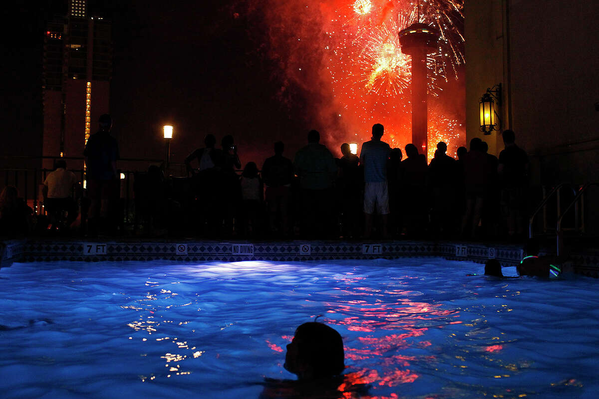 Children swim and people watch fireworks from the Hilton Palacio del Rio pool during the Stars & Stripes over San Antonio inaugural event on Wednesday, July 4, 2012.
