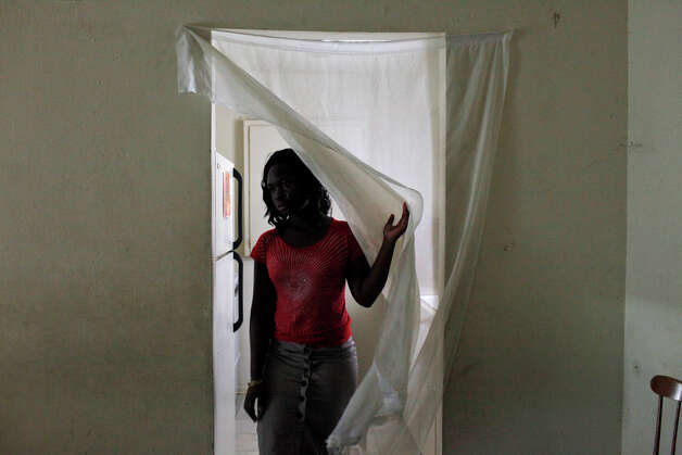 Congolese refugee Faida Lambere, 17, walks out of the kitchen in the apartment she shares her mother and seven siblings at Auburn Creek Apartments in San Antonio on Saturday, July 14, 2012. The family is facing eviction from the apartment this week. Photo: Lisa Krantz, San Antonio Express-News / San Antonio Express-News