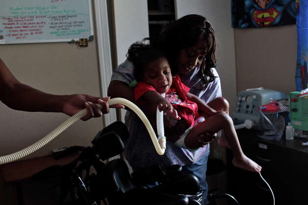 Noni Battle, RN, lifts Braylon Nelson, 2, who was paralyzed in a road rage accident, from his bed to his chair at his home in San Antonio on Friday, June 29, 2012. Nelson receives 24-hour nursing care. Photo: Lisa Krantz, San Antonio Express-News / San Antonio Express-News