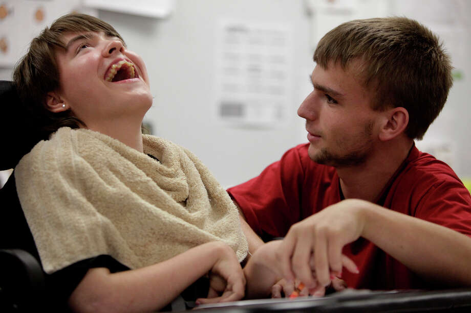 Kassie Sanchez laughs as Adrian Pressey helps her draw a smiley face at Clark High School on Thursday, May 10, 2012. Adrian and Kassie have been friends since elementary school. Photo: Lisa Krantz, San Antonio Express-News / San Antonio Express-News