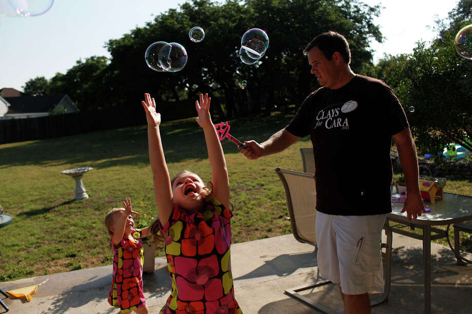 Justin Hobbs and his daughters, Hailey, 4, and Kate, 2, play with bubbles at their home in Fair Oaks Ranch on Saturday, June 9, 2012. Photo: Lisa Krantz, San Antonio Express-News / 2012 San Antonio Express-News