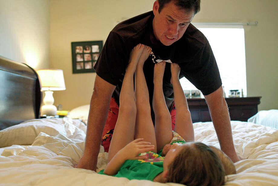 Justin Hobbs plays with his daughters, Hailey, 4, left, and Kate, 2, after their bath before bedtime in his bedroom at their home in Fair Oaks Ranch on Saturday, June 9, 2012. Photo: Lisa Krantz, San Antonio Express-News / 2012 San Antonio Express-News