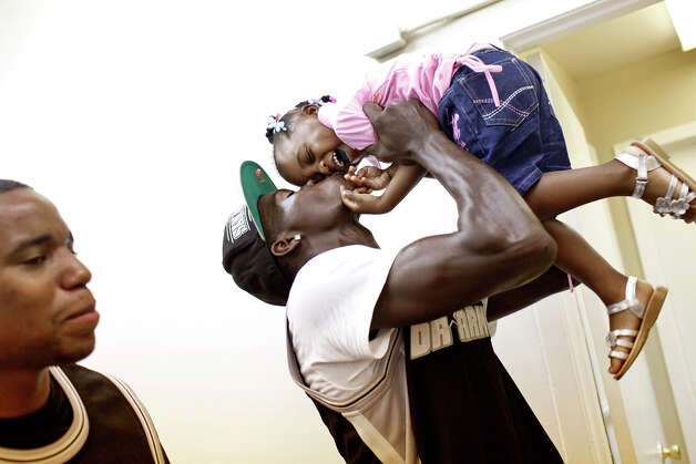 "Brandon Brown, a member of the group ""15Five Da Army,"" kisses his daughter, J'Niah Brown, 2, next to fellow group member, Isaac Ward, left, after the group performed ""I Believe in Me"" and ""Black & Silver,"" their song about the Spurs, during the grand opening celebration at the Eastside Coalition Center, with the Truth MusIQ Movement, in San Antonio on Saturday, June 9, 2012. Photo: Lisa Krantz, San Antonio Express-News / 2012 San Antonio Express-News"