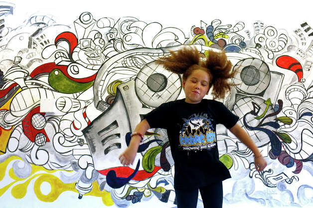 Eliana Dillard, 8, dances to music in the dance room where classes will be taught at the Eastside Coalition Center, with the Truth MusIQ Movement, during the grand opening celebration for the center in San Antonio on Saturday, June 9, 2012. Photo: Lisa Krantz, San Antonio Express-News / 2012 San Antonio Express-News