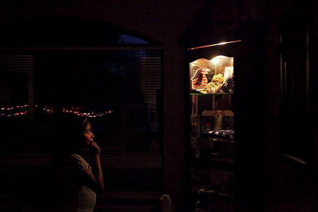 Emma Romero, 8, looks at the display cabinet which stands in tribute to her uncle, Sgt. Mario Rodriguez, Jr., who was killed in Afghanistan in June of 2010, which holds his medals, flags, military certificates and other items from his life, after his mother and Romero's grandmother, Rita Rodriguez, turned the light on in it, which she does every night, at Rodriguez's home in Smithville on Wednesday, May 23, 2012. Photo: Lisa Krantz, San Antonio Express-News / SAN ANTONIO EXPRESS-NEWS