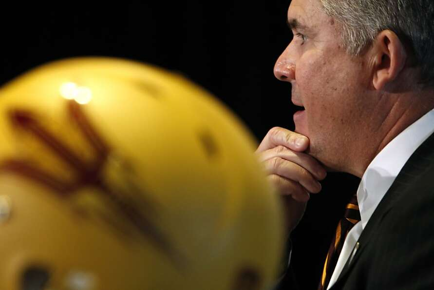 Arizona State head coach Todd Graham speaks with a reporter as players and coaches for Arizona State