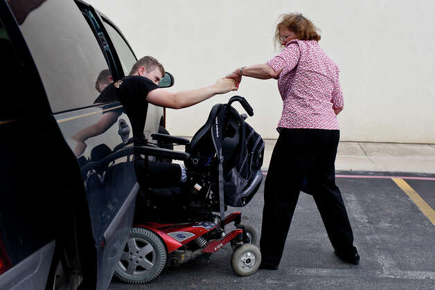 Saralee Trimble helps her son, Army Pfc. Kevin Trimble, 19, get out of their van upon their arrival at Dury's Gun Shop in San Antonio on Wednesday, March 7, 2012. Trimble was looking to buy his own hunting rifle, since he's been borrowing one, for hunting trips with wounded warriors. Click to browse all of the EN's most memorable photos of 2012  Photo: Lisa Krantz, San Antonio Express-News / @San Antonio Express-News