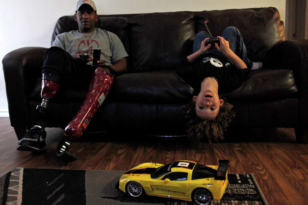 Jonathan Patterson, 7, plays with a new remote controlled car with his father, Ken Patterson, at their home in San Antonio on Tuesday, March 6, 2012. Photo: Lisa Krantz, San Antonio Express-News / @San Antonio Express-News