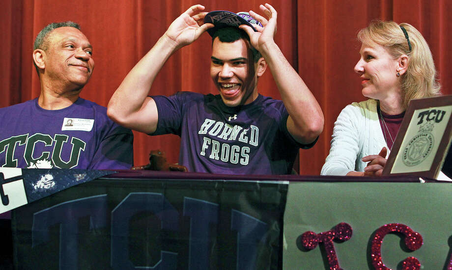 Basketball player Michael Williams tries on his TCU cap after signing while his parents, Bailey Williams and Joann Williams, look on as thirteen athletes commit at early signing day at Reagan High School on November 14, 2012. Photo: Tom Reel, San Antonio Express-News / ©2012 San Antono Express-News