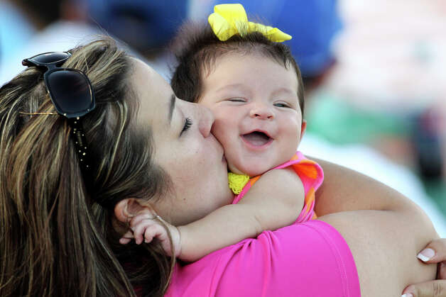 Leila Rendon, 3 months, enjoys a kiss from her mom, Heather Rendon as they watch the Missions play the Corpus Christi Hooks at Wolff Stadium on July 24, 2012. Photo: Tom Reel, San Antonio Express-News / ©2012 San Antono Express-News