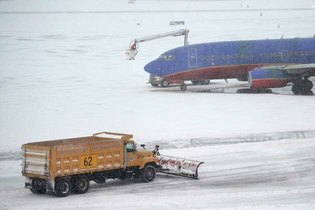 Airport snow plows work around the Southwest flight to Chicago Midway this morning due to the inclement weather both here in Colonie, N.Y. and in the Chicago area Dec 27, 2012. (Skip Dickstein/Times Union) Photo: SKIP DICKSTEIN