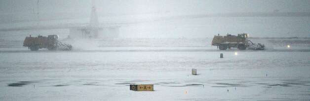 Airport snow plows try to stay ahead of the snow to keep the main runway clear at the Albany International Airport in  Colonie, N.Y. and in the Chicago area Dec 27, 2012. (Skip Dickstein/Times Union) Photo: SKIP DICKSTEIN