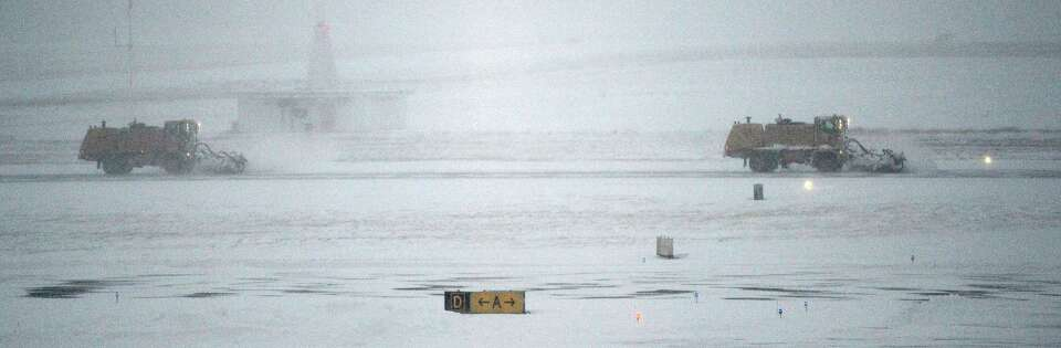 Airport snow plows try to stay ahead of the snow to keep the main runway clear at the Albany Interna