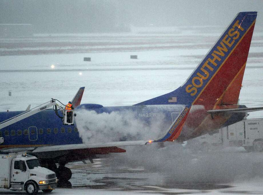 Airport workers deice a Southwest flight at the Albany International Airport in  Colonie, N.Y. and in the Chicago area Dec 27, 2012. (Skip Dickstein/Times Union) Photo: SKIP DICKSTEIN
