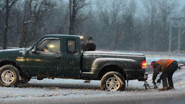 A car which spun out near Exit 5 of the I 87 southbound is winched up on to a tow vehicle in Latham, N.Y. and in the Chicago area Dec 27, 2012. (Skip Dickstein/Times Union) Photo: SKIP DICKSTEIN