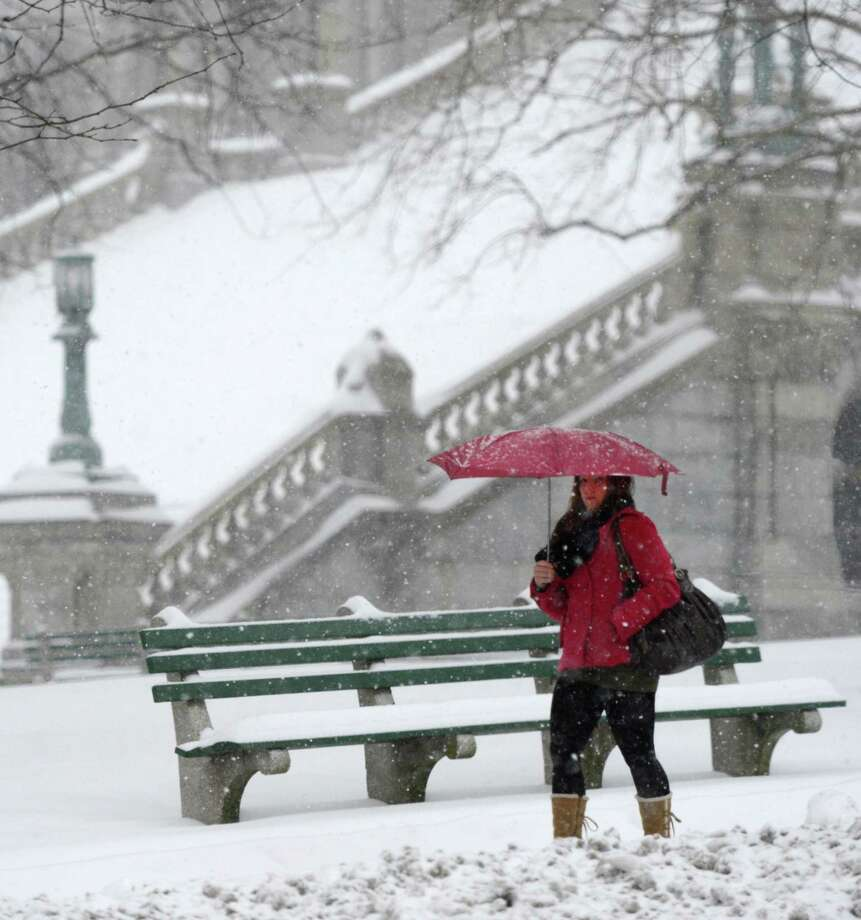 A woman uses an umbrella to protect her from the snow near the State Capitol building in Albany, N.Y. Dec 27, 2012. (Skip Dickstein/Times Union) Photo: SKIP DICKSTEIN