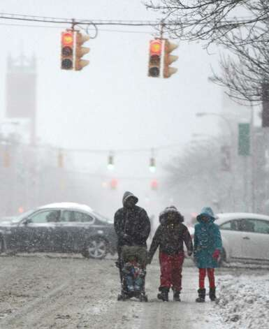 Pedestrians take to the streets to get to their destination due to the snowfall in Albany, N.Y. Dec 27, 2012. (Skip Dickstein/Times Union) Photo: SKIP DICKSTEIN