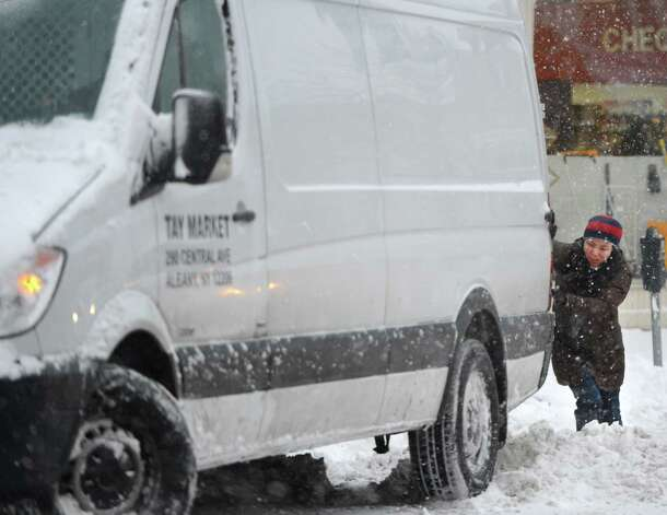 A person assists a van that was snowed in on Central Avenue in Albany, N.Y. Dec 27, 2012. (Skip Dickstein/Times Union) Photo: SKIP DICKSTEIN
