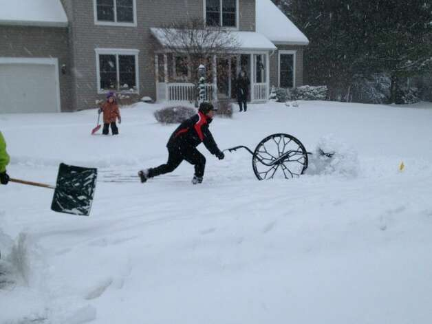 Matt Reiner of Guilderland uses his back-safe, eco-friendly ergonomic wheel snow shovel on Thursday, Dec. 27, 2012. (Paul Grondahl/Times Union)