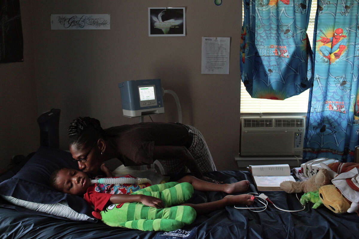 Rhodena Matthews kisses her grandson, Braylon Nelson, 2, at his home in San Antonio. Braylon was paralyzed last year in a road rage accident.
