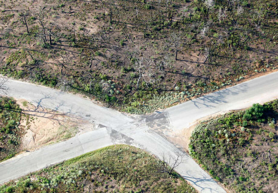 A road intersection seen by many in a widely distributed Sept. 6, 2011 aerial image is seen almost one year after the Bastrop Fire Complex fire in a second aerial image taken Monday Aug 20, 2012. Photo: William Luther / © 2012 San Antonio Express-News