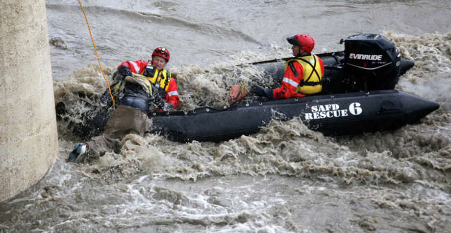 Santos Olivo, 26, is rescued Wednesday July 11, 2012 from the San Antonio River at the Roosevelt Avenue overpass by firefighters from Station 11.