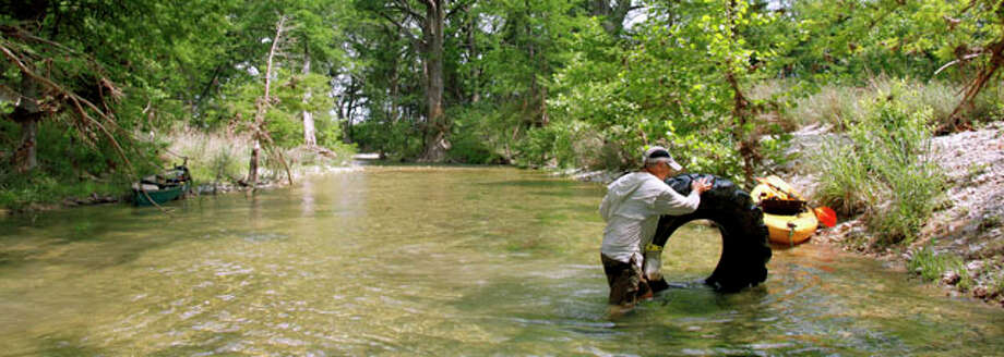 Medina River Cleanup coordinator Bob Brischetto works Tuesday May 1, 2012 on the stretch of the Medina River between Three Mile Bridge on Hwy 16 and Peaceful Valley Road  to move a tractor tire on to the river bank during a scouting scouting trip in advance of the organization's May 5 clean-up. The river was running at about 20 cubic feet per second, far below the average for this time of year. Photo: William Luther / © 2012 WILLIAM LUTHER