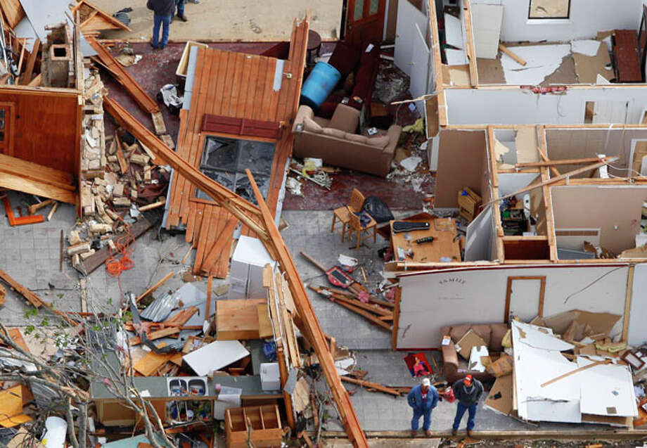 Two men stand  (bottom center of image) in the ramains of a house damaged from an overnight tornado in the Devine area, as seen in this Tuesday March 20, 2012 aerial image. Photo: William Luther / © 2012 WILLIAM LUTHER