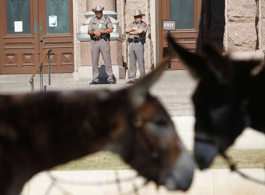 Capitol police officers watch a protest Wednesday Jan. 18, 2012 outside the capitol in Austin as members of the Wild Burro Protection League gather after they delivered a petition to the governor's office asking him to order the Texas Parks and Wildlife Department to stop killing wild burros in Big Bend Ranch State Park.Click to browse all of the EN's most memorable photos of 2012  Photo: William Luther / © 2012 SAN ANTONIO EXPRESS-NEWS