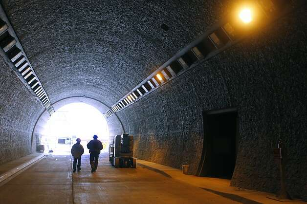 Construction workers walk towards the portal on the south end of the northbound Devil's Slide tunnel in Pacifica, Calif. on Friday, Dec. 21, 2012. Caltrans plans to open the twin bores early next year. Photo: Paul Chinn, The Chronicle