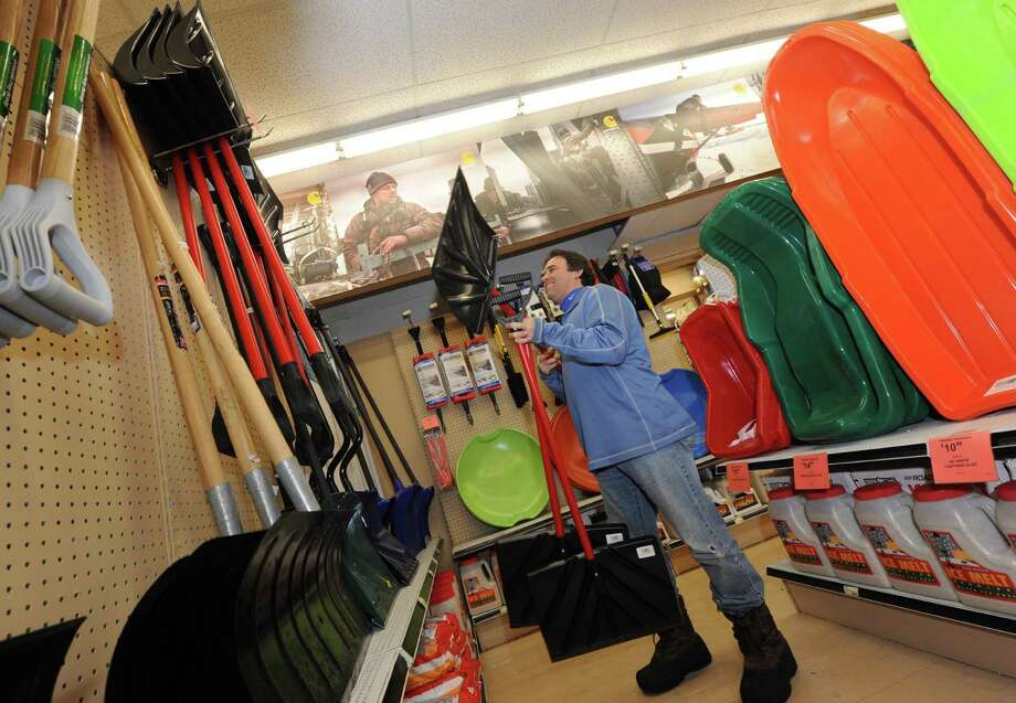 Jon Phillips, owner of Phillips Hardware on Central Avenue, stocks shovels at his store in Colonie, N.Y., Thursday Dec. 27 2012. (Michael  P. Farrell/Times Union) Photo: Michael P. Farrell