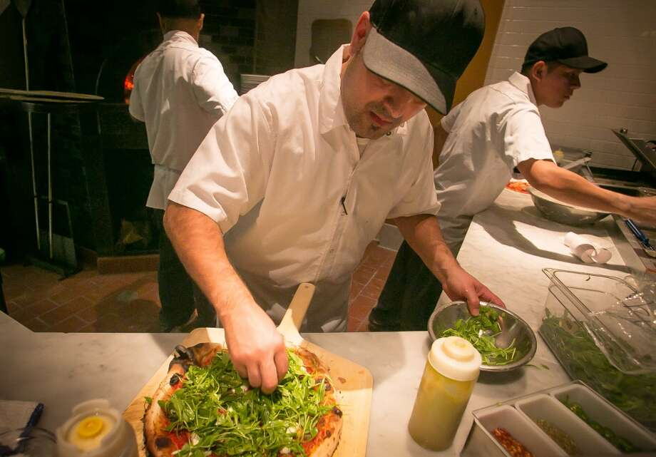 Paul Aguirre puts arugula on a pizza. (Special to the Chronicle)