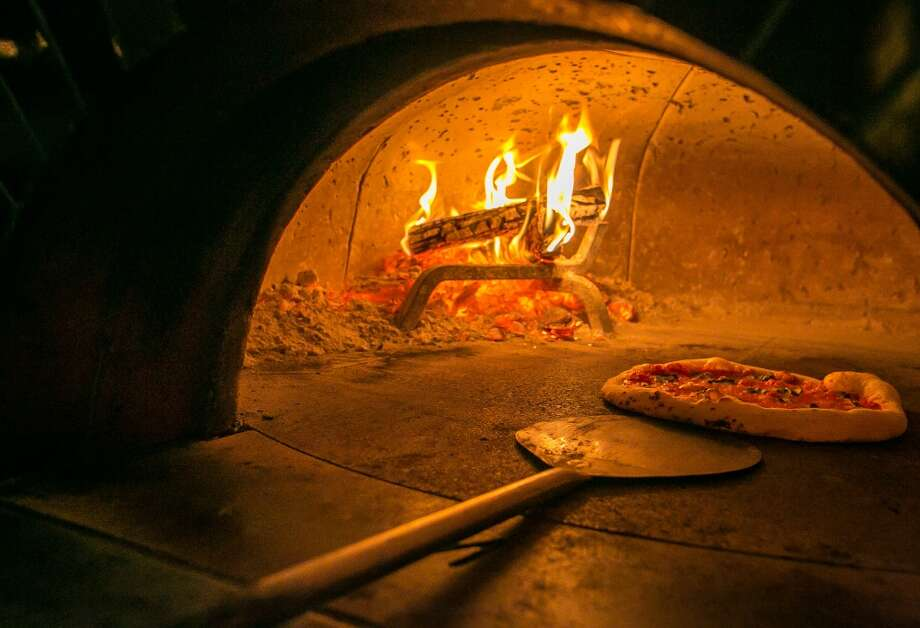 Pizzas cooking in the wood burning oven at Vesta. (Special to the Chronicle)