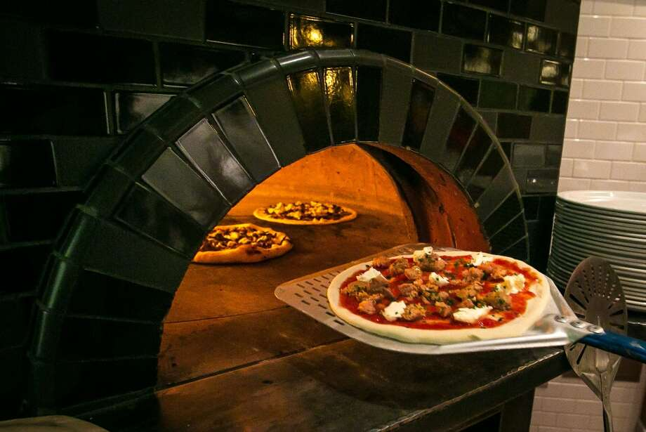 A pizza goes into the wood burning oven at Vesta. (Special to the Chronicle)