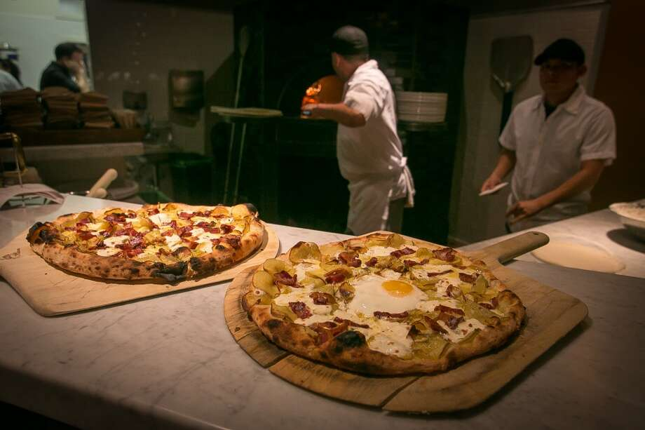 Two Sausage and Honey pizzas fresh from the oven, one with a farm egg, at Vesta. (Special to the Chronicle)